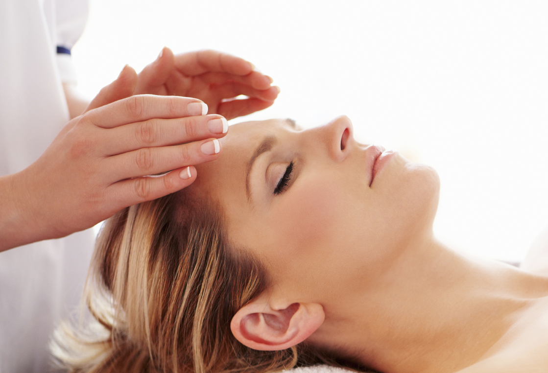 Person receiving Reiki, hands over forehead